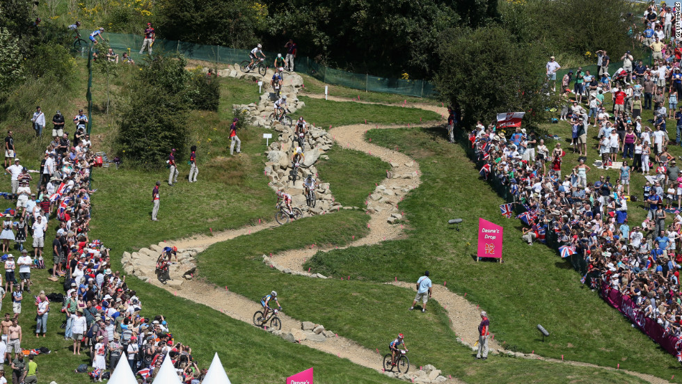 Women's cross-country mountain bike competitors race down Deane's Drop, a section of the course named for a school.