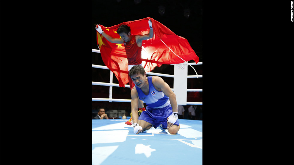 Kaeo Pongprayoon of Thailand, in blue, reacts as Shiming Zou of China waves the Chinese national flag after being declared winner in the light flyweight boxing final.