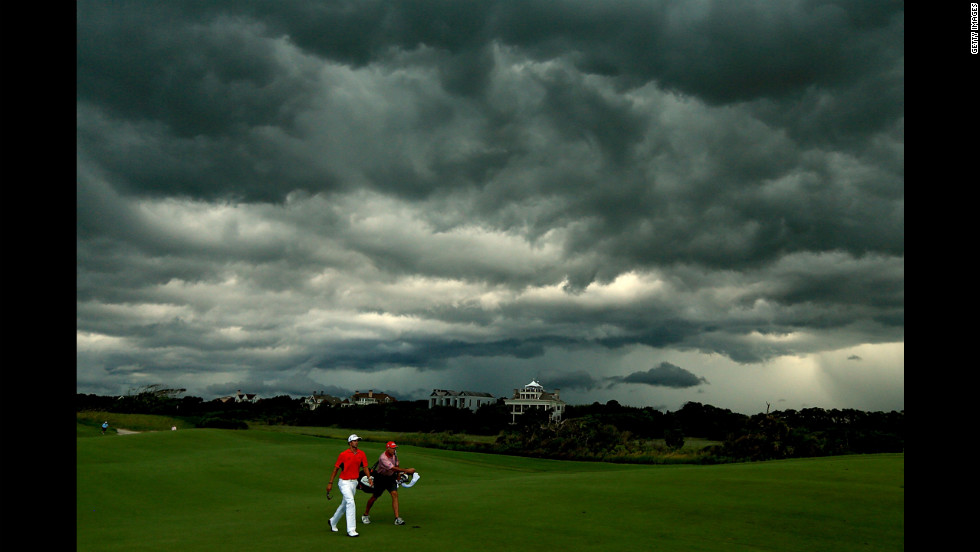 Adam Scott of Australia walks off the course under dark clouds as play is suspended due to rain on Saturday, August 11.