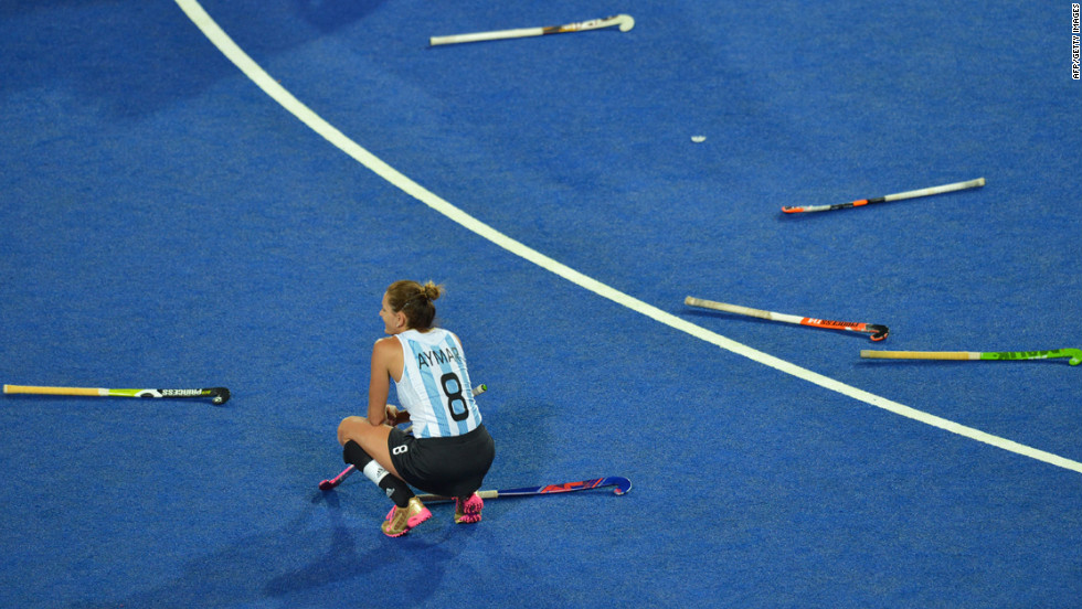 Argentina's Luciana Aymar sits among discarded sticks after her team's defeat in the women's field hockey gold medal match between Netherlands and Argentina.