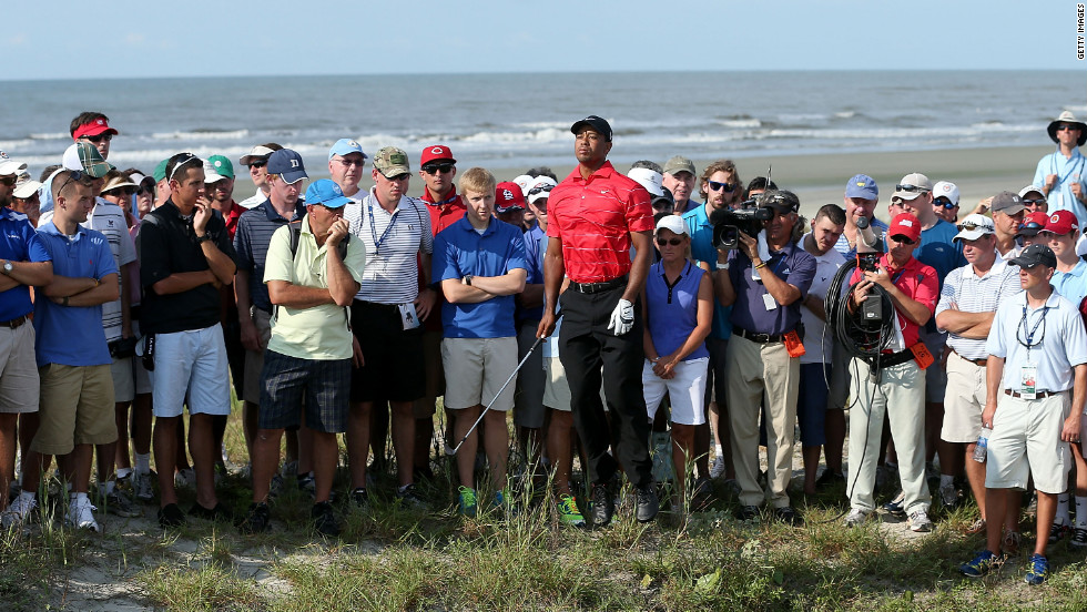 Surrounded by the gallery, Woods jumps to see his ball after his shot on the15th hole.