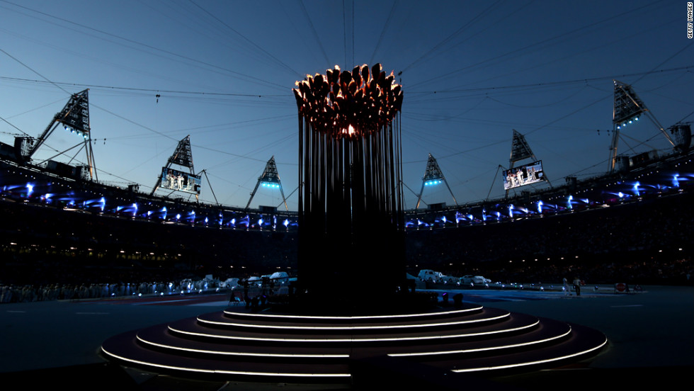 The Olympic Cauldron burns at the center of the stadium.