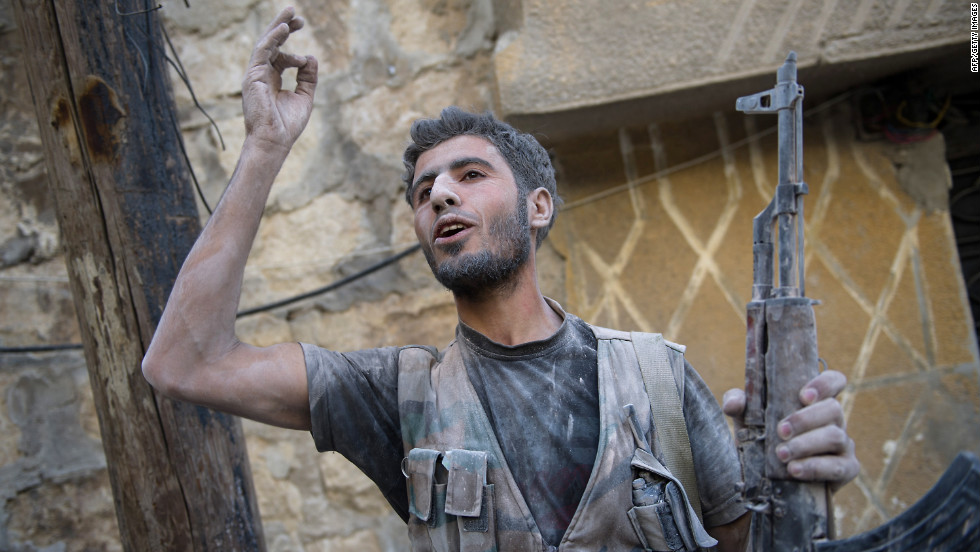 A rebel fighter gestures toward others after emerging from a shelled building during fighting Monday with government forces.