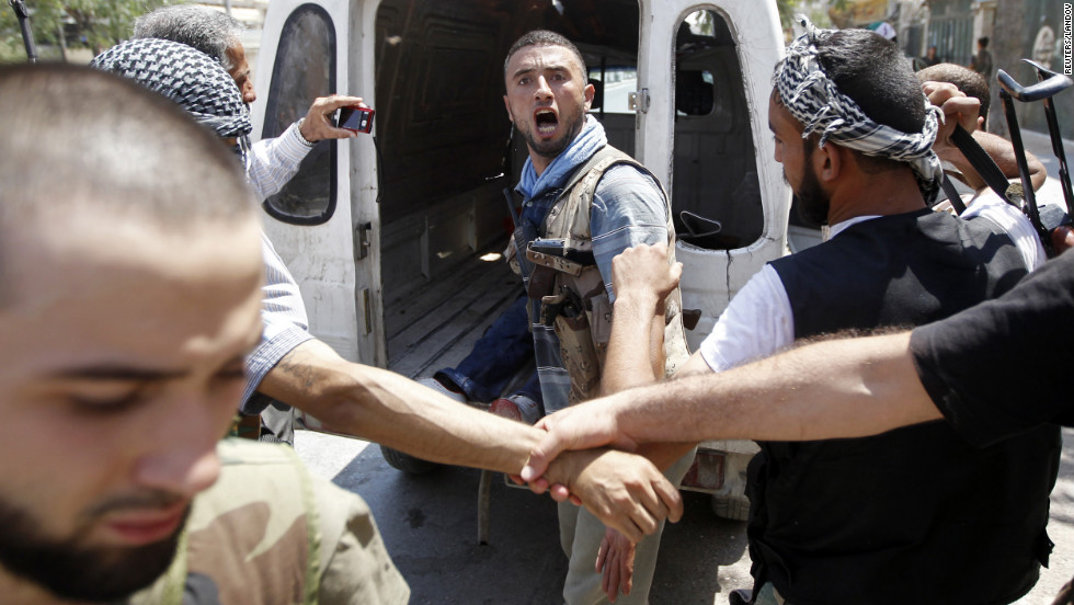 A Free Syrian Army fighter learns that his commander has been killed by a tank shell in Aleppo on Tuesday, August 14. Opposition activists say shelling in dissident strongholds has exacerbated the humanitarian crisis in the country.