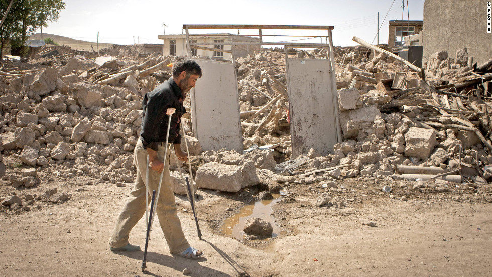 A man walks past the debris of a destroyed building in Ahar in northwest Iran on Monday, August 13. Two earthquakes that hit northwestern Iran killed more than 300 people and injured more than 3,000.