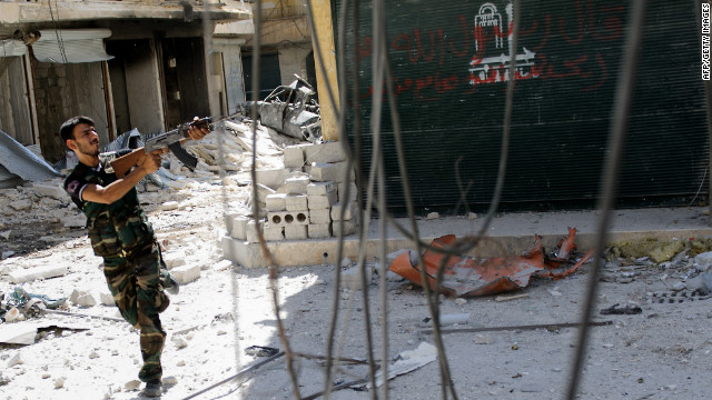 A Syrian rebel aims his weapon as he tries to dodge pro-government sniper fire while running across a street in the Salaheddin district of the northern city of Aleppo on August 13, 2012.