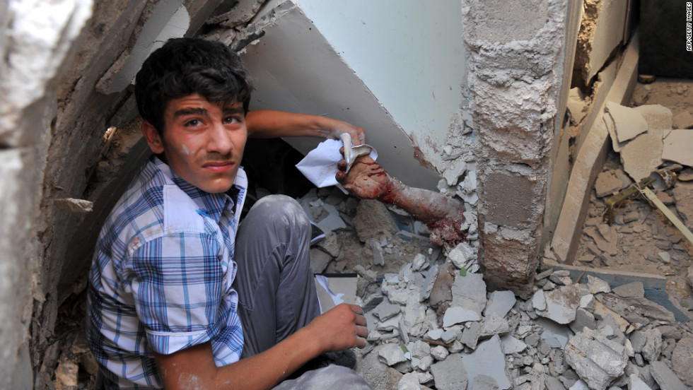 A Syrian youth holds the arm of someone trapped under rubble after an airstrike in the town of Azaaz, on the outskirts of Aleppo.