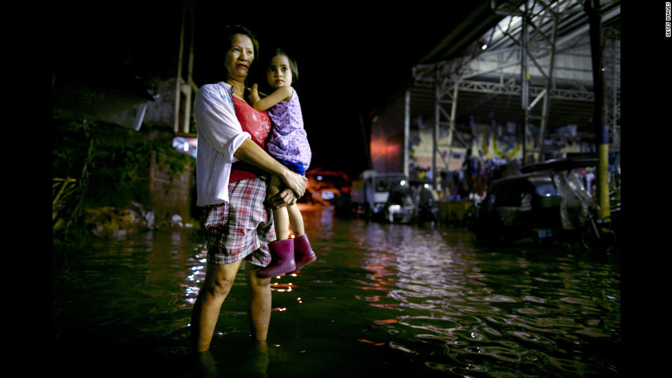 Precy Magtalas holds her daughter Kristine outside their home next to the Pampanga River.