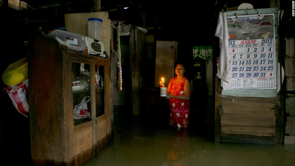 A woman lights her flooded home with a candle in Bulacan.