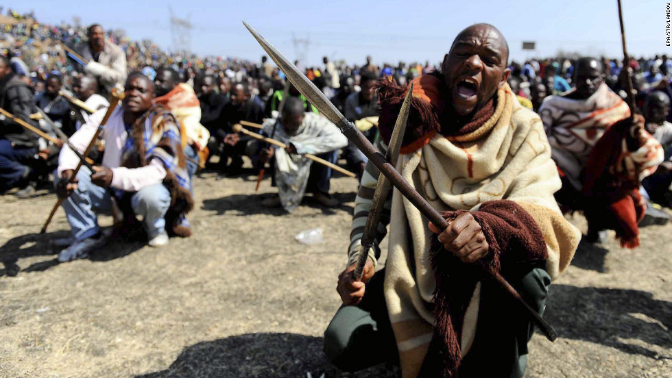 Striking South African miners armed with homemade spears and pangas chant slogans near the Marikana platinum mine on  August 16, 2012. Rising tensions at the mine exploded into grisly violence after police opened fire on striking miners.