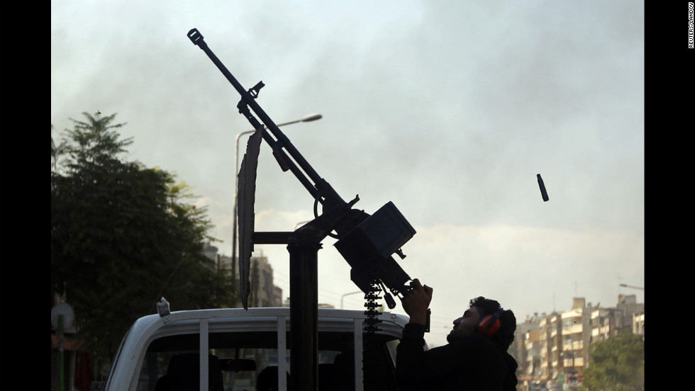 A Free Syrian Army fighter fires an anti-aircraft gun at a Syrian air force helicopter in Aleppo on Thursday, August 16.