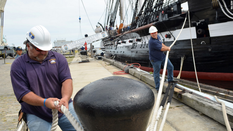 Members of the Naval History and Heritage Command secure the USS Constitution to the pier after Sunday's demonstration.