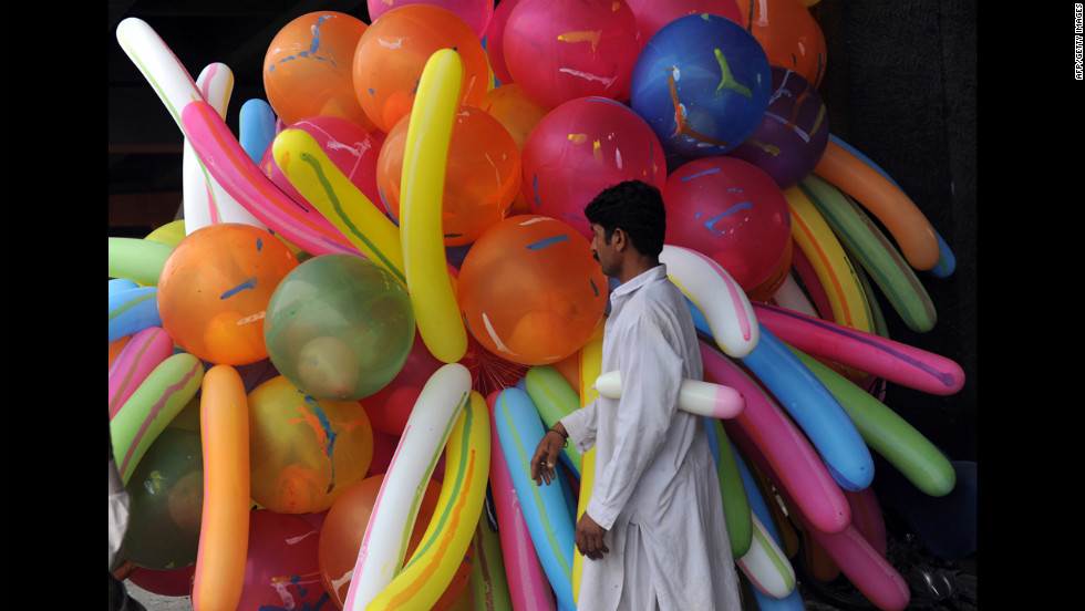 A Pakistani balloon vendor waits for customers near a mosque where Muslims offer Eid al-Fitr prayers in Karachi on Monday.