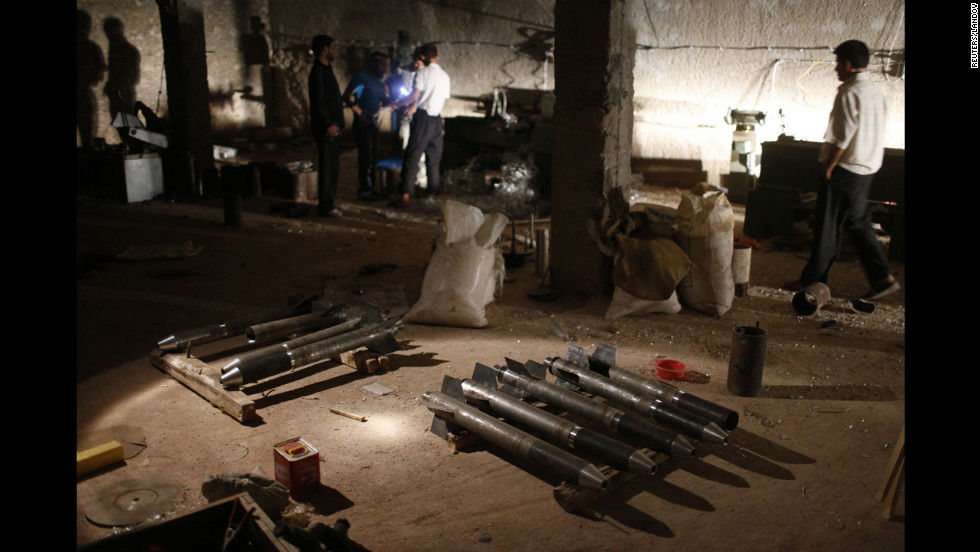 Syrian rebel fighters stand around a cache of homemade missiles which they say they will use on forces loyal to president Bashar al-Assad in Aleppo on August 21.