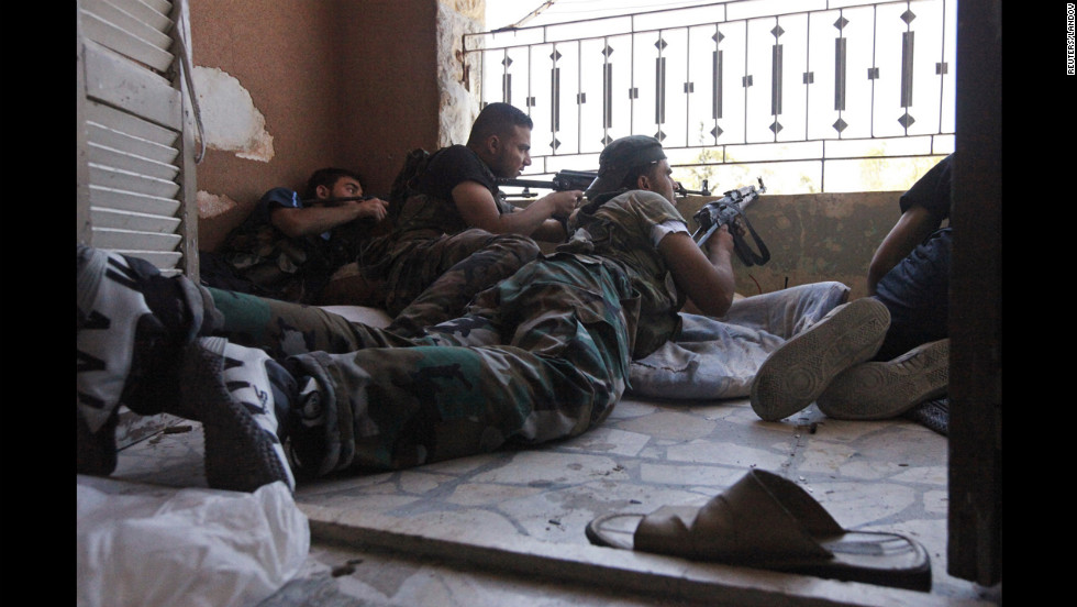 Members of the Free Syrian Army take cover during clashes with Syrian Army soldiers on August 22.