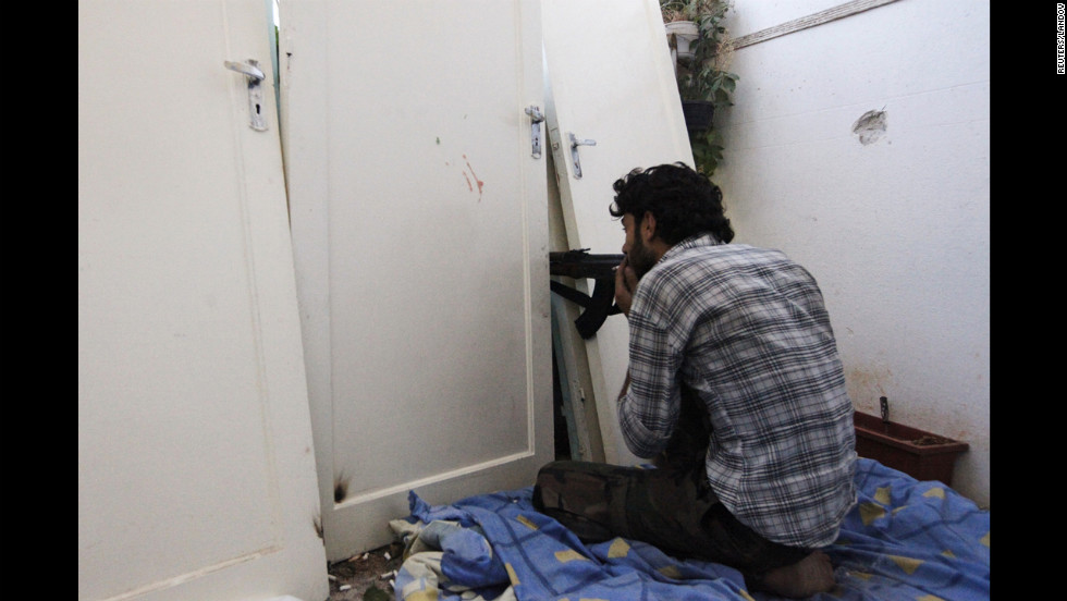 A member of the Free Syrian Army aims his rifle as he uses doors as a shield on August 22.