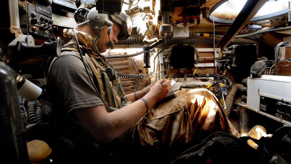 Prince Harry sitting below the turret of his Spartan armored vehicle as he communicates with other units by radio, in the desert in Helmand province in Southern Afghanistan, on February 20, 2008. The 23-year-old, an officer in the Household Cavalry regiment, secretly served for several weeks in the volatile southern province of Helmand.