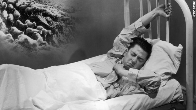 A man fights a losing battle with insomnia by counting sheep.