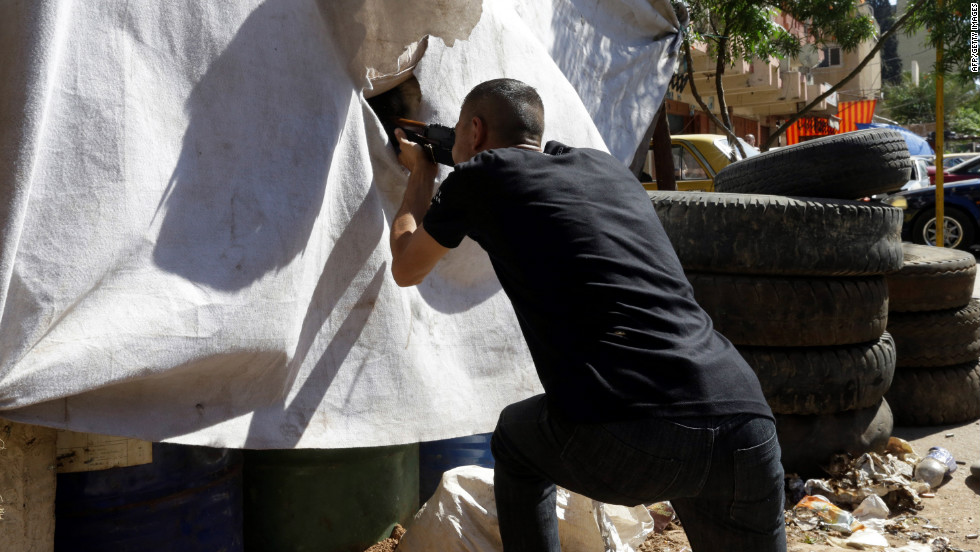 An opponent of the Syrian regime gets ready to fire during clashes Wednesday in Tripoli's Bab al Tabaneh neighborhood.