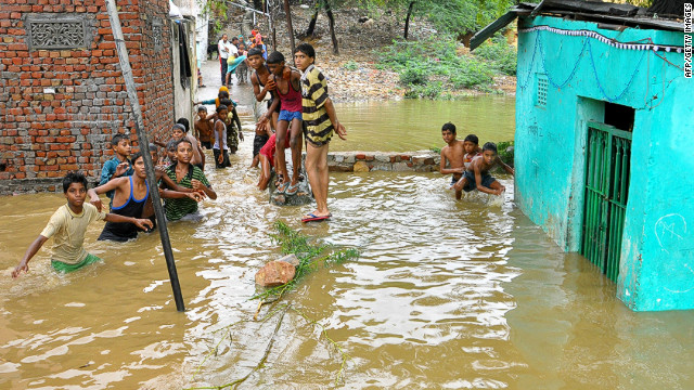 Indian residents wade through floodwaters in Jawahar Nagar colony in Jaipur, the capital of Rajasthan state, on August 23.