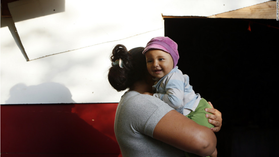 A woman from the Roma community carries a child in a camp in Evry.