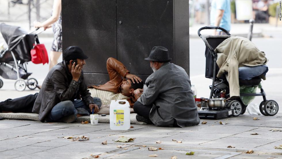 Roma men while away the hours at the Place de la Bastille in Paris.