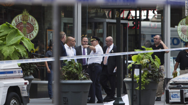 Law enforcement stands near the covered body of the suspected shooter near the Empire State Building on August 24.