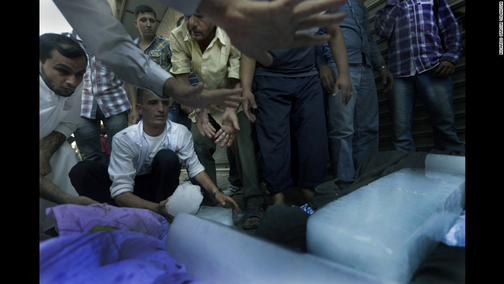 People gather around the bodies of an entire family killed by the airstrike the day before on Friday, August 17, in front of a hospital.