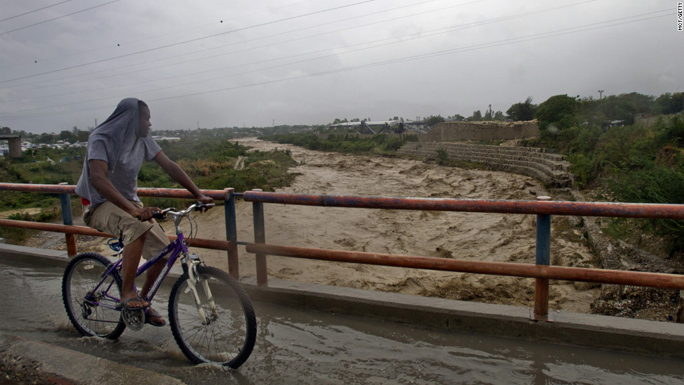 A young man rides his bike by the rising water from the Riviere Grise, which runs alongside a tent city in Port-au-Prince.