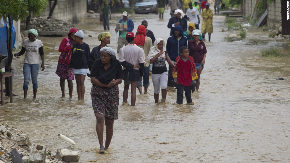 Residents flee their flooded homes with their possessions.