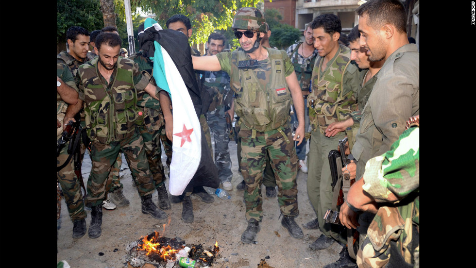 A handout picture released by SANA shows army soldiers burning a revolution flag in Aleppo.
