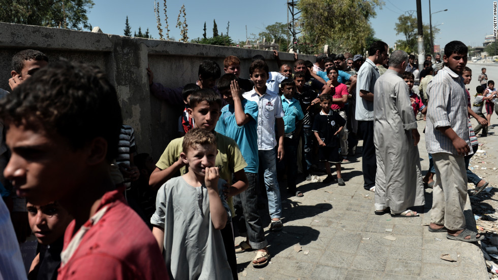 Residents line up along a street in Aleppo as they wait to receive free bread.