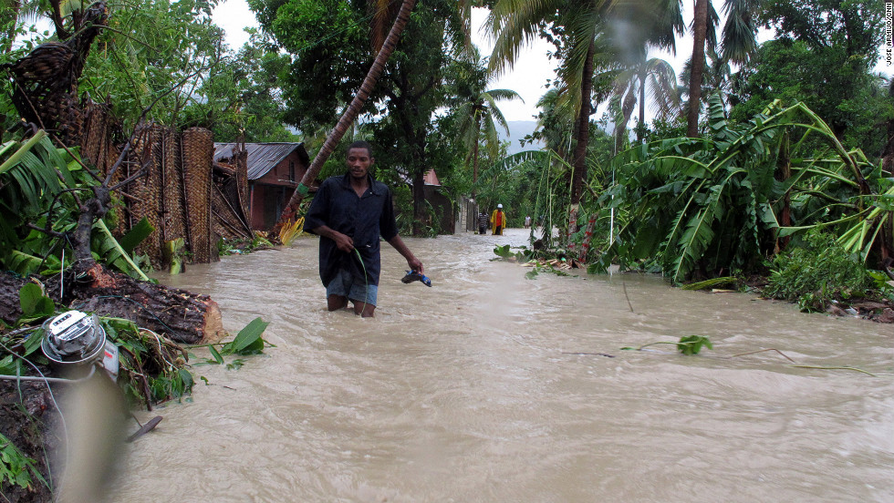 Residents of Jacmel make their way through floodwaters as Tropical Storm Isaac dumps heavy rains on Saturday.