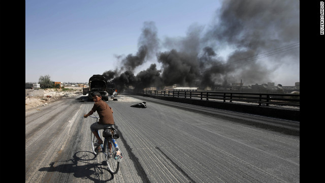 A boy rides a bicycle toward smoking fuel trucksin the Bab al-Nayrab district of Aleppo on  August 27,.  The trucks were struck by missiles fired by a figter jet.