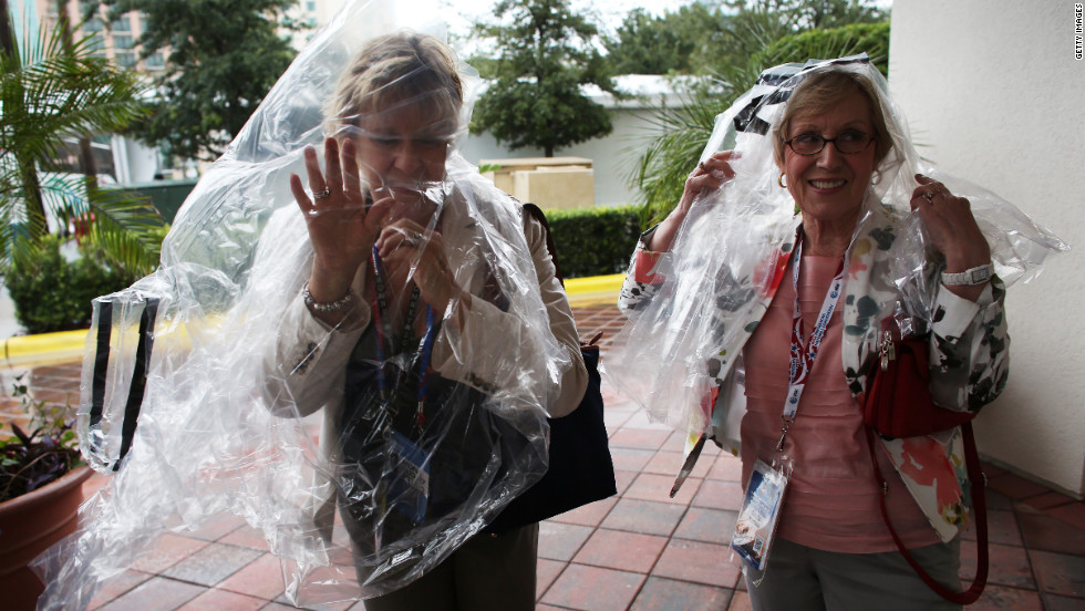 Two convention-goers wear plastic bags as shelter from the rain caused by Tropical Storm Isaac.