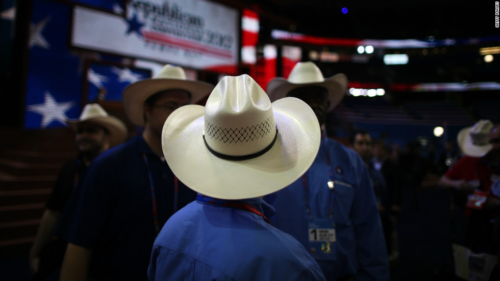 Men wearing cowboy hats stand on the arena floor before the start of the abbreviated first day.
