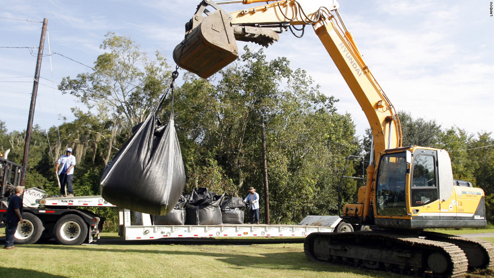 A crew from Jefferson Parish Drainage Department places large sandbags near a canal and pond in Jean Lafitte, Louisiana, on Monday in preparation for Isaac.