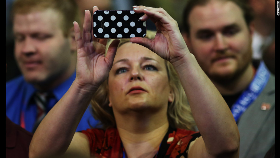 A woman captures the goings-on with her phone before the start of the shortened first day of the Republican National Convention.