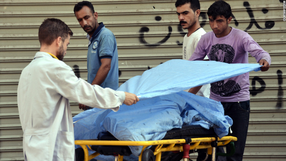 A paramedic and another man cover the body of a Free Syrian Army fighter outside a hospital in Aleppo.
