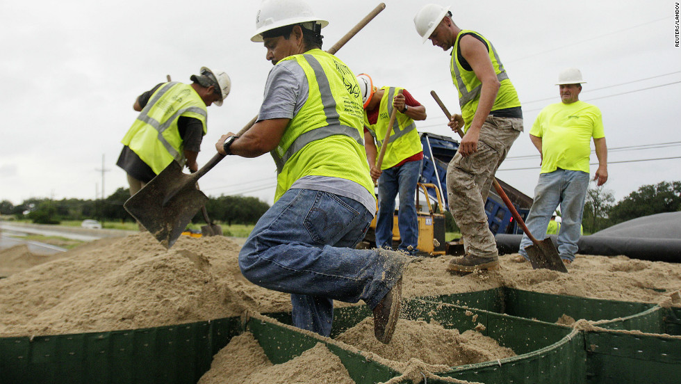 Workers try to close off state Highway 23 South in Oakville, Louisiana, on Tueday as Issac heads toward the coast.