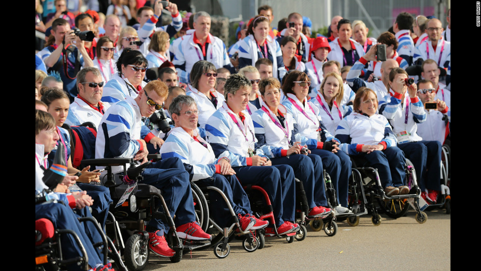 Members of Team GB Paralympic look on as they are welcomed by dancers during a ceremony at the Paralympic Village.