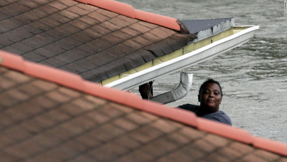 Hanging from her roof, a woman waits to be rescued by New Orleans Fire Department workers on August 29, 2005.