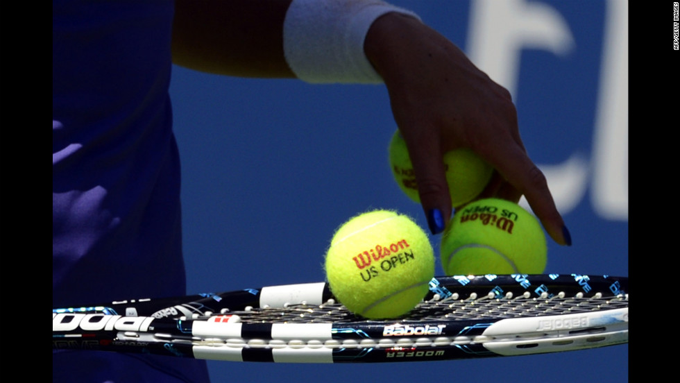 Agnieszka Radwanska of Poland selects tennis balls during a match against Nina Bratchikova of Russia.