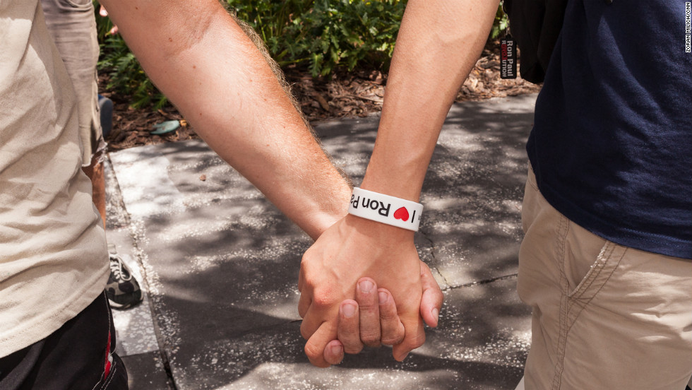 Ron Paul supporters hold hands at a rally for the only challenger to Mitt Romney who has not conceded.