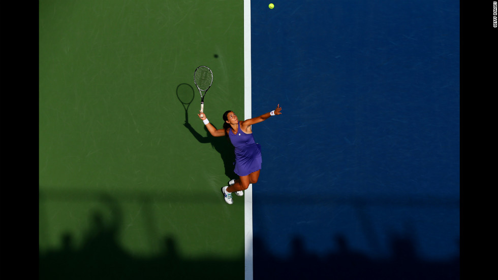 France's Marion Bartoli serves during her women's singles first-round match against American Jamie Hampton.