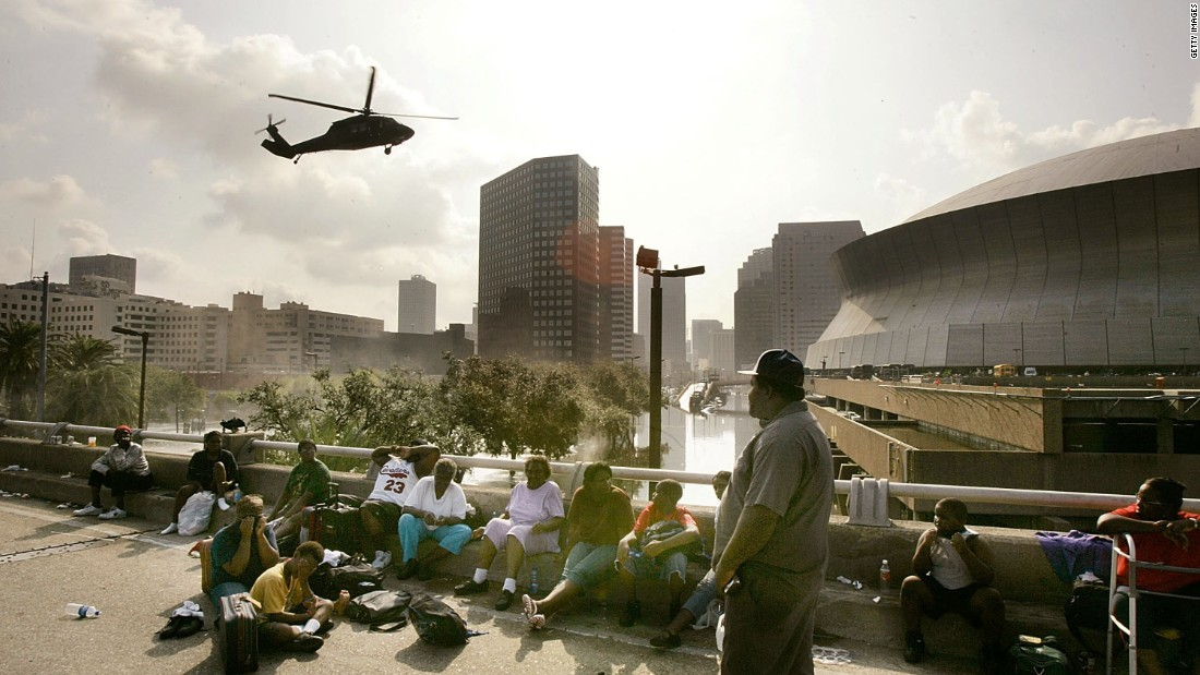 People seek high ground on Interstate 90 as a helicopter prepares to land at the Superdome in New Orleans on August 31, 2005.
