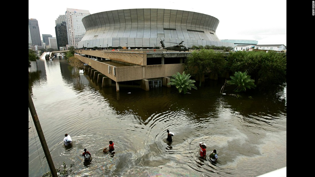 People wade through high water in front of the Superdome in New Orleans on August 30, 2005.