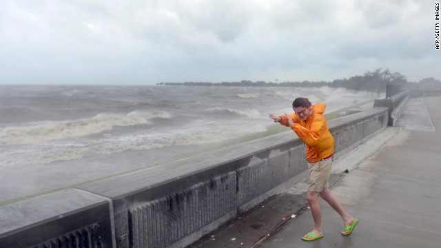 """Evan Stoudt faces strong winds while visiting the banks of Lake Pontchartrain in New Orleans on August 28, 2012 in Louisiana, where Hurrican Isaac has made landfall.  The US National Hurricane Center said a """"dangerous storm surge"""" was occuarring along the northern Gulf Coast with storm surges of up to eight feet (2.4 meters) already being reported in Louisiana, Mississippi and Florida.  States of emergency have been declared in Louisiana and Mississippi, allowing authorities to coordinate disaster relief and seek emergency federal funds. AFP PHOTO / Frederic J. BROWN        (Photo credit should read FREDERIC J. BROWN/AFP/GettyImages)"""