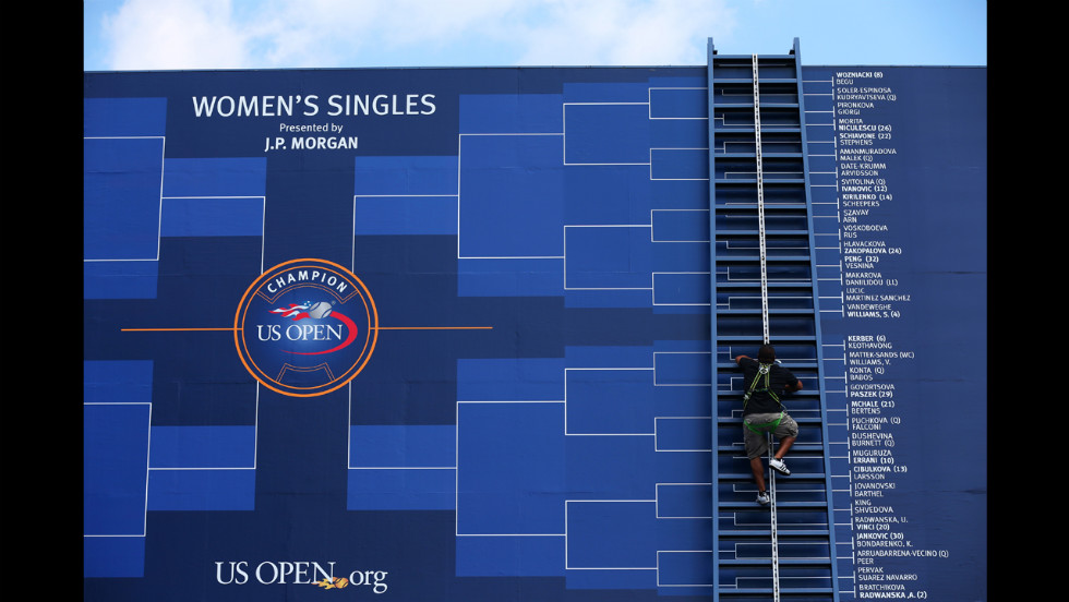A worker climbs a ladder to adjust the board displaying the women's draw.