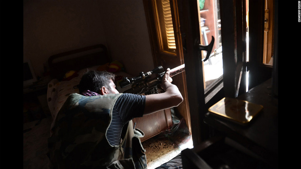 A Syrian opposition fighter aims a sniper rifle at government forces in Aleppo on Wednesday, August 29.